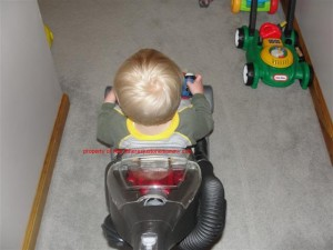 toddler on vacuum cleaner