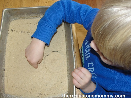 practicing writing letters in sand