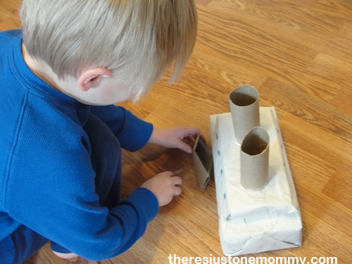 preschooler playing with cardboard box craft