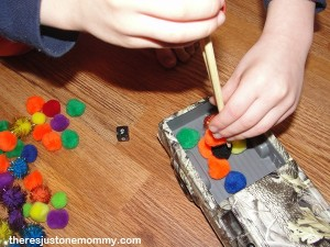 working on fine motor skills with chopsticks and pom-poms