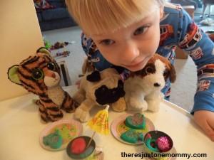 preschooler serving pretend cookies to stuffed animals