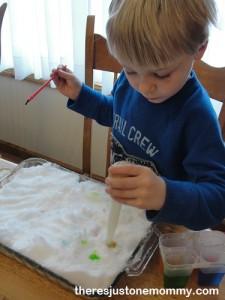 preschooler painting snow