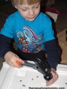 boy hammering nails in styrofoam