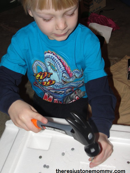 boy hammering nails in styrofoam