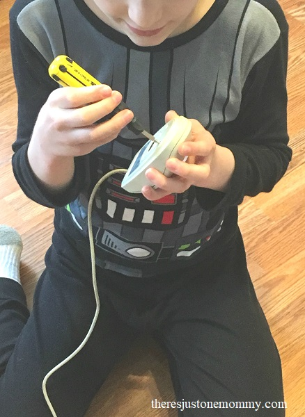 upcycled STEM activity: child taking apart computer pieces