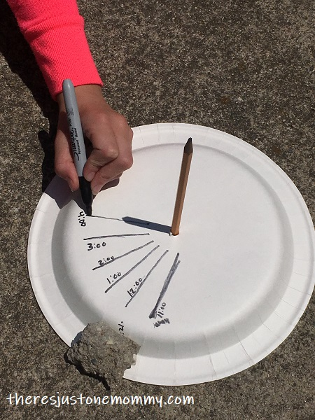 child drawing lines on paper plate sundial